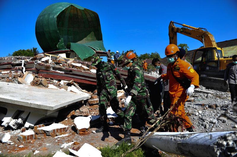 LOMBOK, Aug. 7, 2018 - Members of Indonesian search and rescue team carry a bag containing a dead body in North Lombok, Indonesia, on Aug. 7, 2018. The Sunday Lombok earthquake has killed 98 people, ...