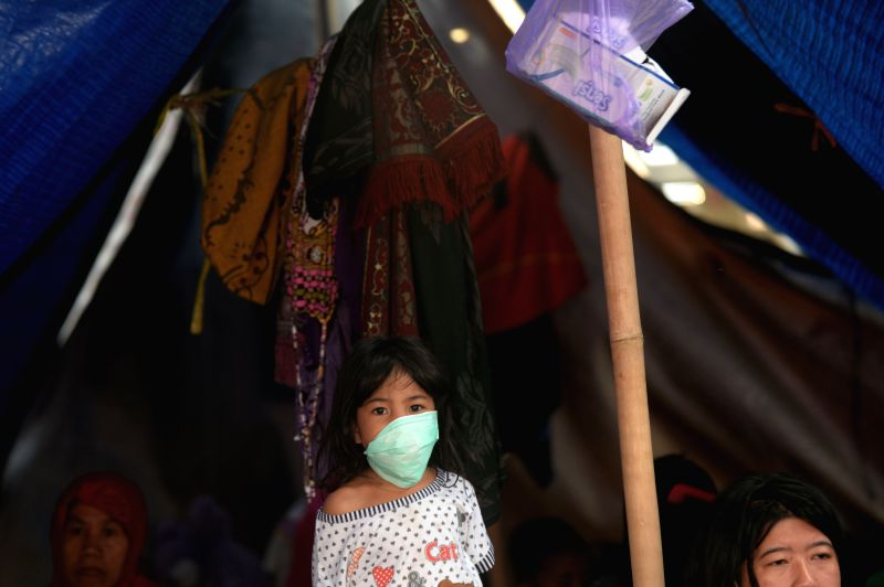 LOMBOK, Aug. 9, 2018 - A girl wears a mask at a temporary shelter in Tanjung, North Lombok, Indonesia, Aug. 9, 2018.