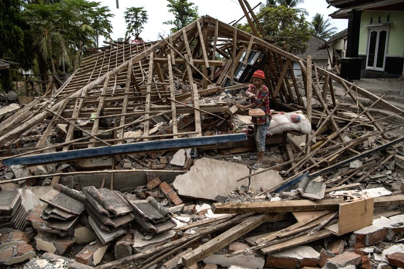 LOMBOK, Aug. 9, 2018 - A resident passes by a collapsed building in Lombok island, Indonesia, on Aug. 9, 2018. A 5.9-magnitude aftershock struck Lombok island in central Indonesia on Thursday four ...
