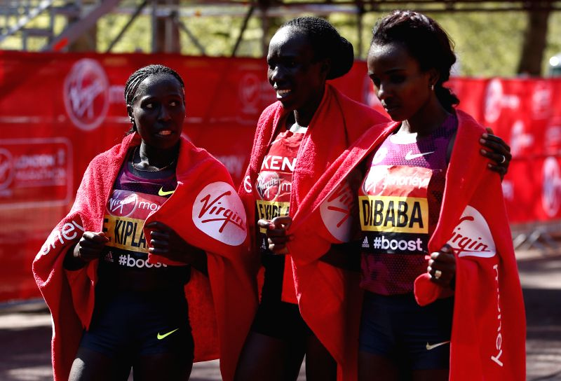 Edna Kiplagat (C) of Kenya poses with her compatriot Florence Kiplagat (L) and Tirunesh Dibaba of Ethiopia after crossing the finish line of 2014 London Marathon in .