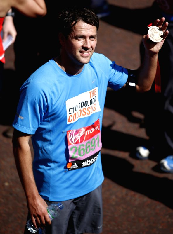Michael Owen, English former footballer, poses after crossing the finish line of 2014 London Marathon in London, Britain on Apr. 13, 2014. Michael Owen finished the .