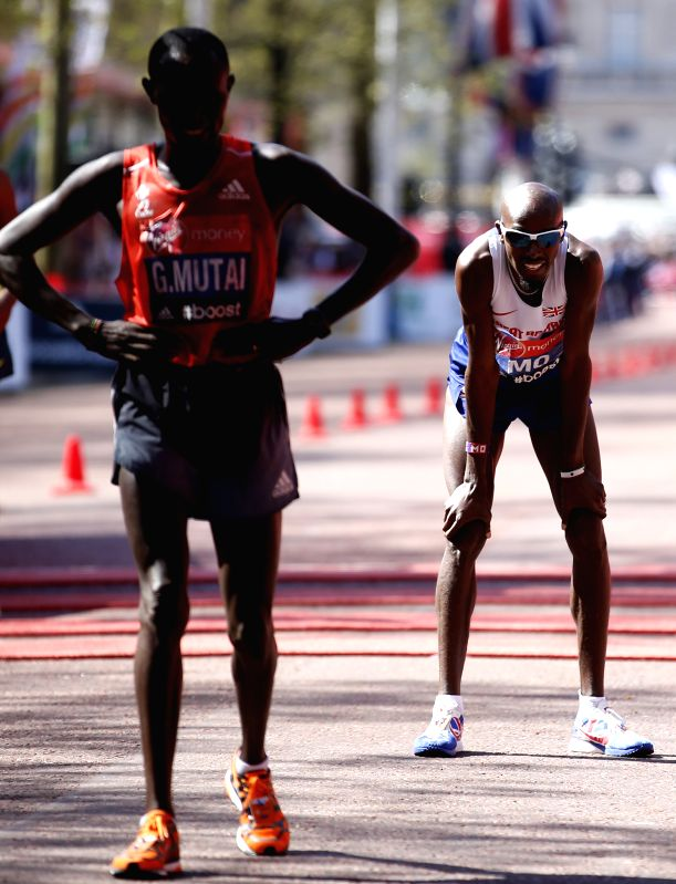 Mo Farah (R) of Great Britain reacts after crossing the finish line of 2014 London Marathon in London, Britain on Apr. 13, 2014. Mo Farah took the eighth place of ...