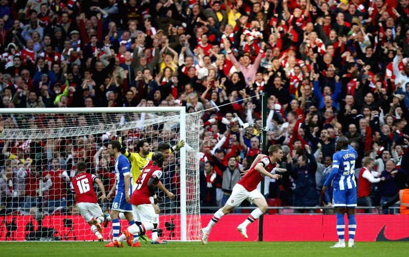 Per Mertesacker (2nd, R) of Arsenal celebrates scoring during FA Cup semifinal match between Arsenal and Wigan Athletic at Wembley Stadium in London, Britain, on ...