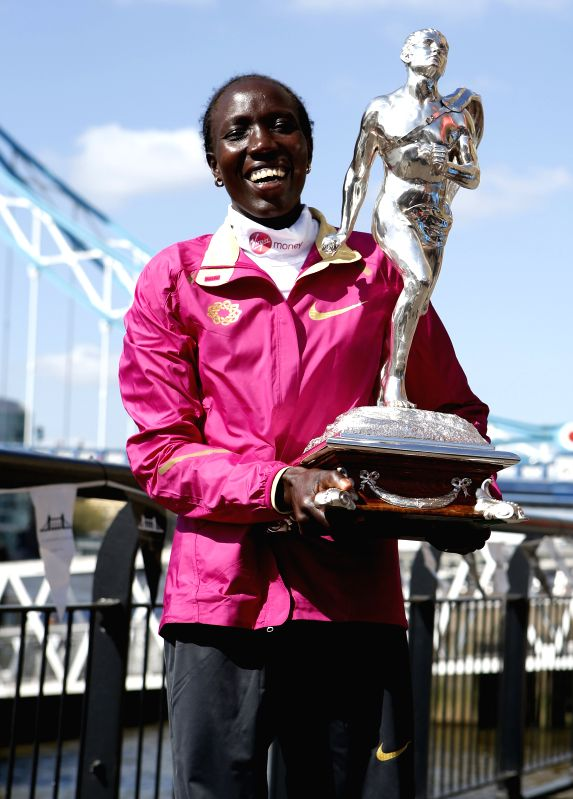 Edna Kiplagat Kenya poses with her trophy during the champions photocall of 2014 London Marathon near Tower Bridge in London, Britain on April 14, 2014. Edna ...