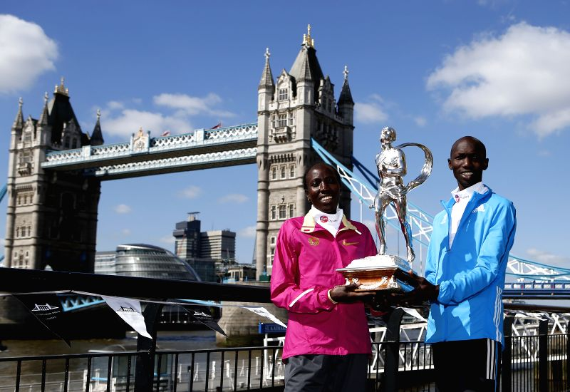 Edna Kiplagat (L) and Wilson Kipsang of Kenya pose with trophies during the champions photocall of 2014 London Marathon near Tower Bridge in London, Britain on ...