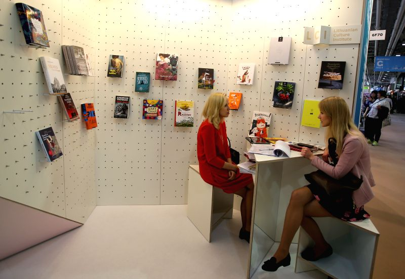 An exhibitor (L) communicates with a visitor at the London Book Fair in Olympia, London, Britain on April 14, 2015. The London Book Fair will be held here from ...