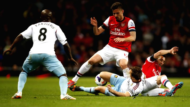 Olivier Giroud (2nd L) and Santiago Cazorla (1st R) of Arsenal vie with Mark Noble (2nd R) of West Ham United during the Barclays Premier League match between ...