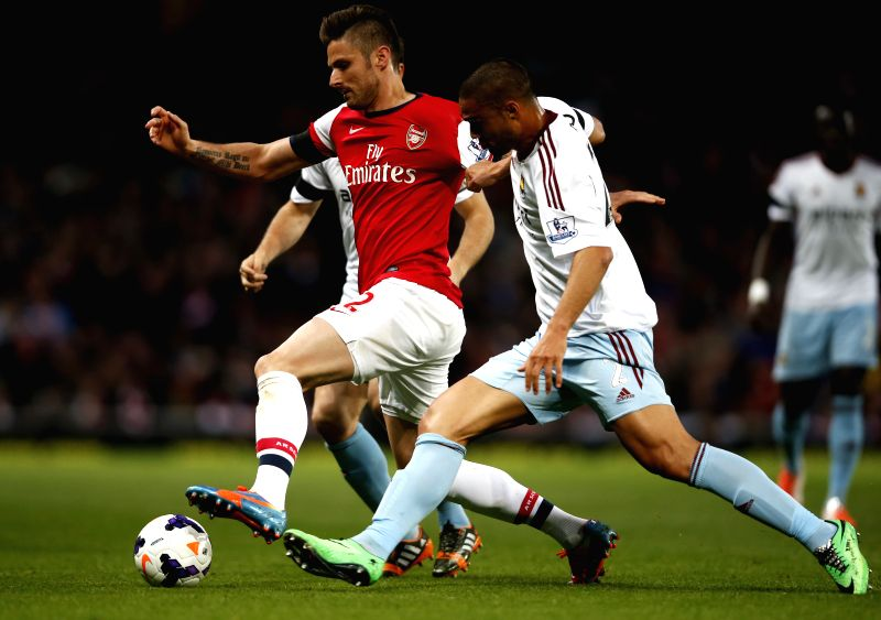 Olivier Giroud (C) of Arsenal vies with Winston Reid(R) of West Ham United during the Barclays Premier League match between Arsenal and West Ham United at Emirates .