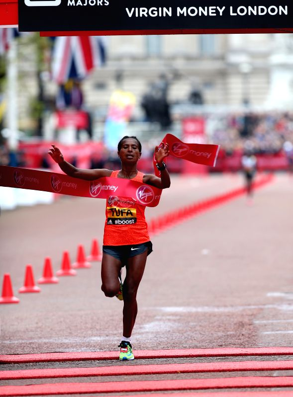 Tigist Tufa of Ethiopia who came first crosses the finish line at the 35th London Marathon, Sunday, April 26, 2015.  Tigist Tufa of Ethiopia won the gold with 2 ...