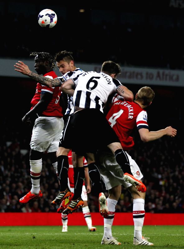 Bacary Sagna(1st L) of Arsenal heads the ball with Mathieu Debuchy (2nd L) of Newcastle during the Barclays Premier League match between Arsenal and Newcastle at ...
