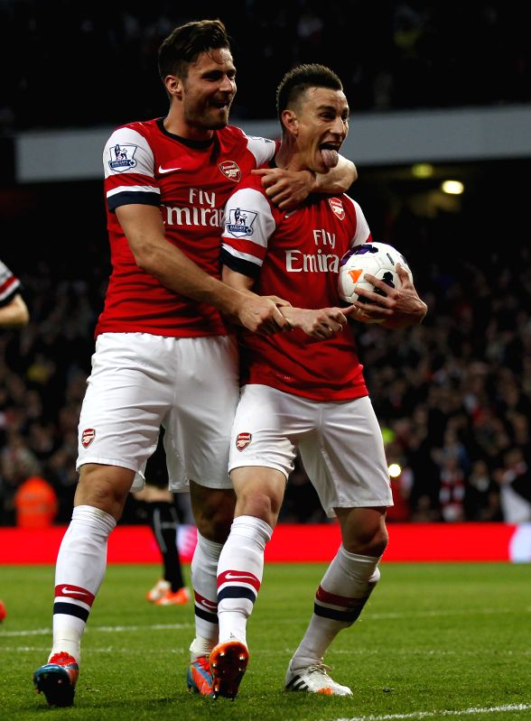 Laurent Koscielny (R) of Arsenal celebrates scoring with teammate Olivier Giroud during the Barclays Premier League match between Arsenal and Newcastle at Emirates .