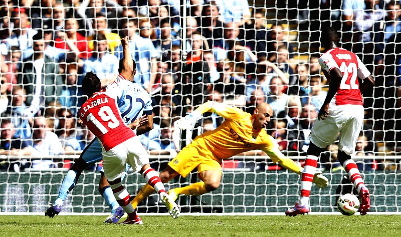 Santi Cazorla (1st, L) of Arsenal scores during the Community Shield match between Arsenal and Manchester City  at Wembley Stadium in London, Britain on Aug. 10, ...