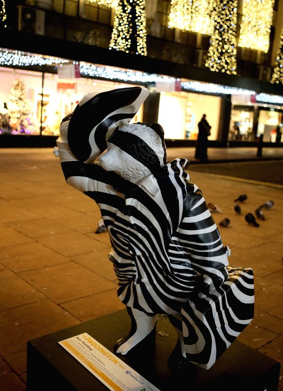 Photo taken on Nov. 19, 2014 shows a Paddington Bear statue in Oxford Street in London, Britain. Paddington Bear is a fictional character in children's literature. ..