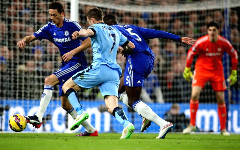 James Milner (2nd L) of Manchester City breaks through the defence of Nemanja Matic (1st L) and Kurt Zouma (2nd R) of Chelsea during the Barclays Premier League match