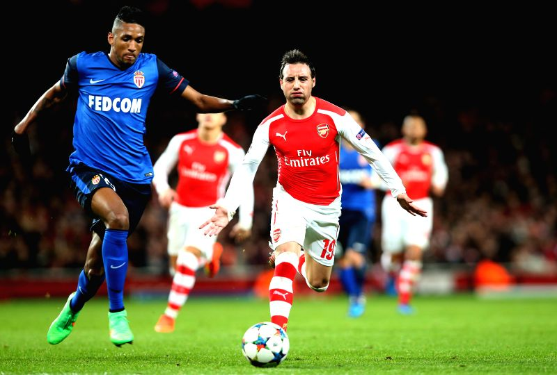 Santi Cazorla (R) of Arsenal vies with Wallace of Monaco during the UEFA Champions league Round of 16 first leg match between Arsenal and Monaco at the Emirates ...