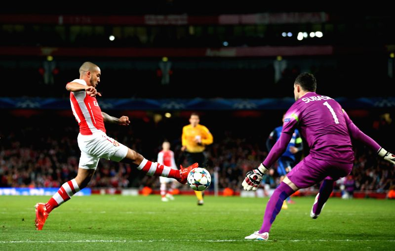 Theo Walcott (L) of Arsenal shoots during the UEFA Champions league Round of 16 first leg match between Arsenal and Monaco at the Emirates Stadium in London, ...