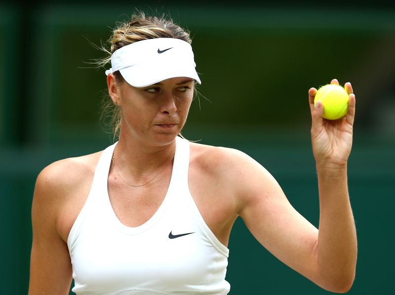Russia's Maria Sharapova holds a ball during the women's singles fourth round match against Germany's Angelique Kerber at the 2014 Wimbledon Championships in ...