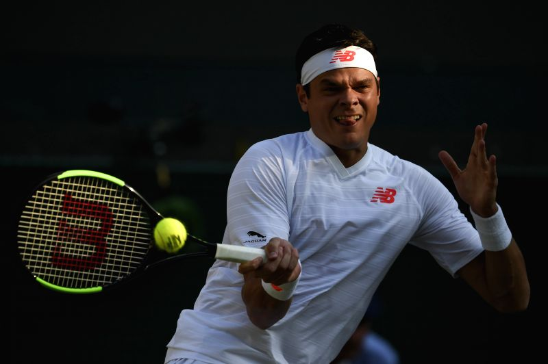 LONDON, July 12, 2018 - Milos Raonic of Canada hits a return during the men's singles quarterfinal match against John Isner of the United States at the Wimbledon Championships 2018 in London, ...