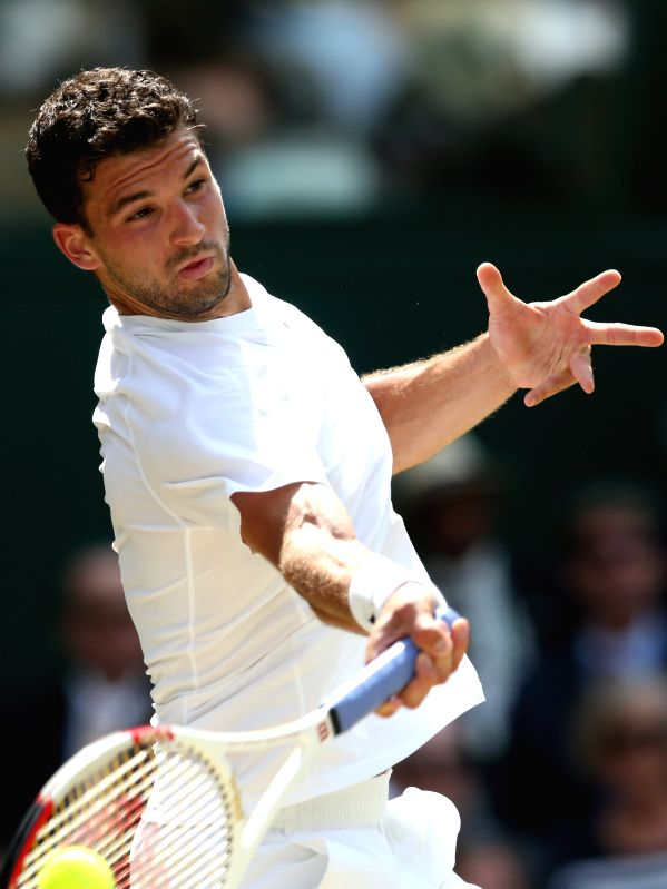 Bulgaria's Grigor Dimitrov returns a shot during the men's singles quarter final against Britain's Andy Murray at the 2014 Wimbledon Championships in Wimbledon, ...