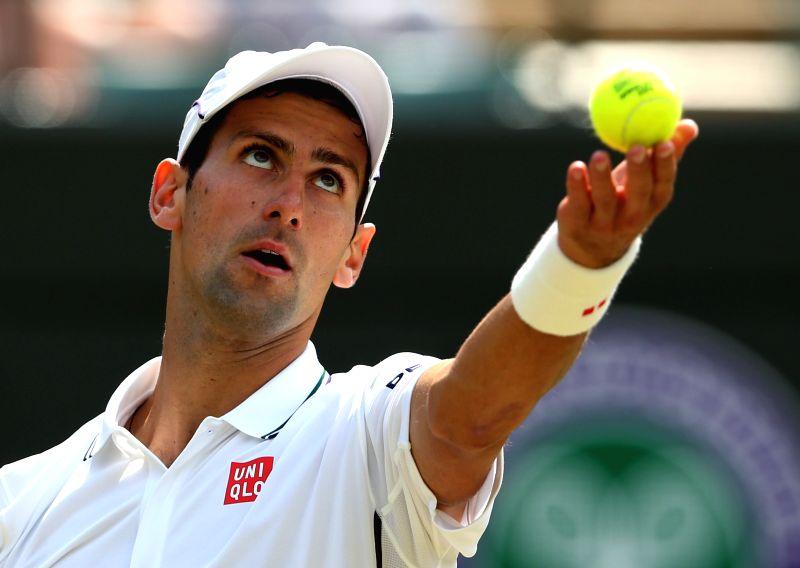 Serbia's Novak Djokovic returns a shot during the men's singles quarter final against Marin Cilic of Croatia at the 2014 Wimbledon Championships in Wimbledon, ...