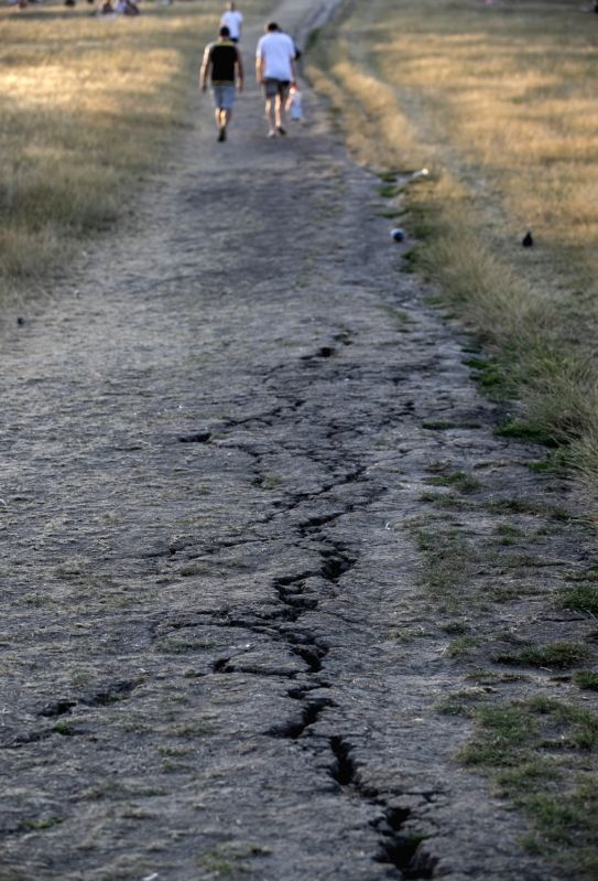LONDON, July 27, 2018 - People pass by dried land in London, Britain on July 26, 2018. Temperatures in the coming days could break all-time UK records, with the mercury set to soar to 37 degree ...