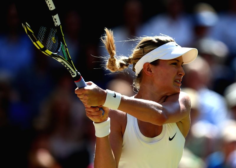 Eugenie Bouchard of Canada returns a shot during the women's singles semi final against Simona Halep of Romania at the 2014 Wimbledon Championships in Wimbledon, ...