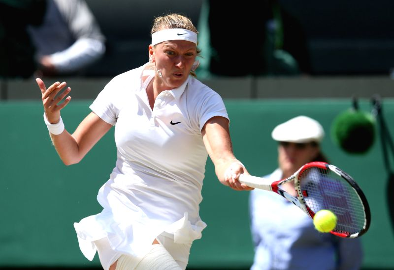 Petra Kvitova of Czech Republic returns a shot during the women's singles semi final against her compatriot Lucie Safarova at the 2014 Wimbledon Championships in ...