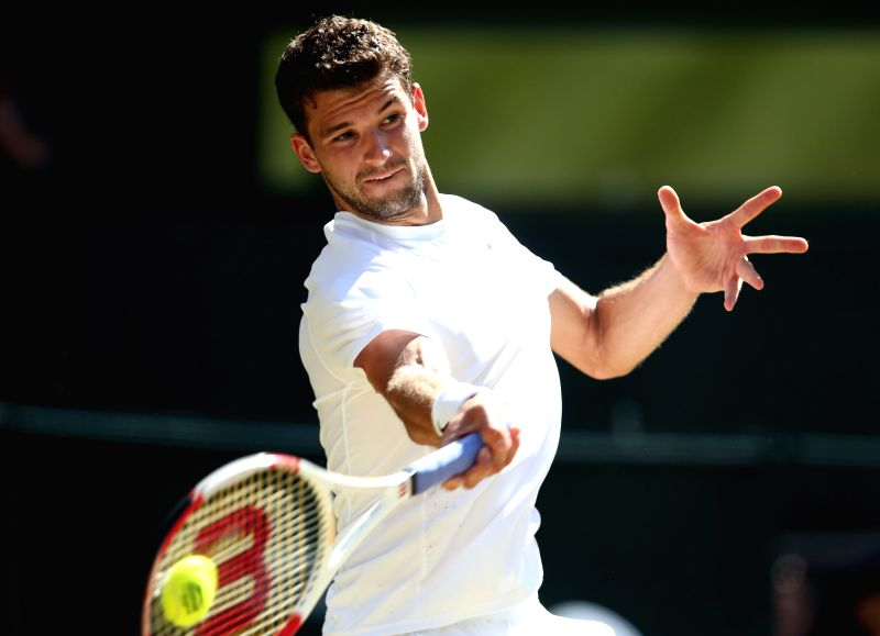 Bulgaria's Grigor Dimitrov returns the ball during the men's singles semi-final match against Serbia's Novak Djokovic at the 2014 Wimbledon Championships in ...