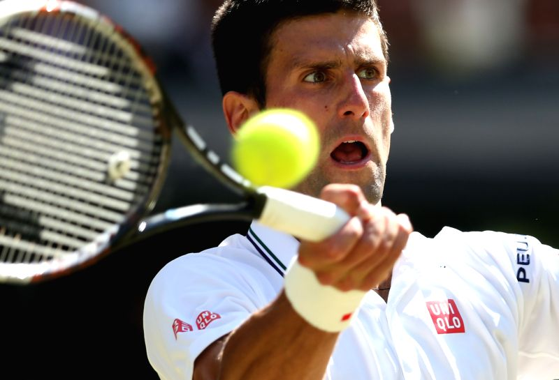 Serbia's Novak Djokovic returns the ball during the men's singles semi-final match against Bulgaria's Grigor Dimitrov at the 2014 Wimbledon Championships in ...