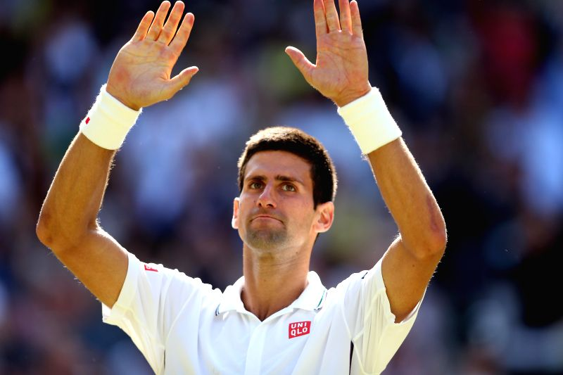 Serbia's Novak Djokovic gestures to spectators after winning the men's singles semi-final match against Bulgaria's Grigor Dimitrov at the 2014 Wimbledon Championships