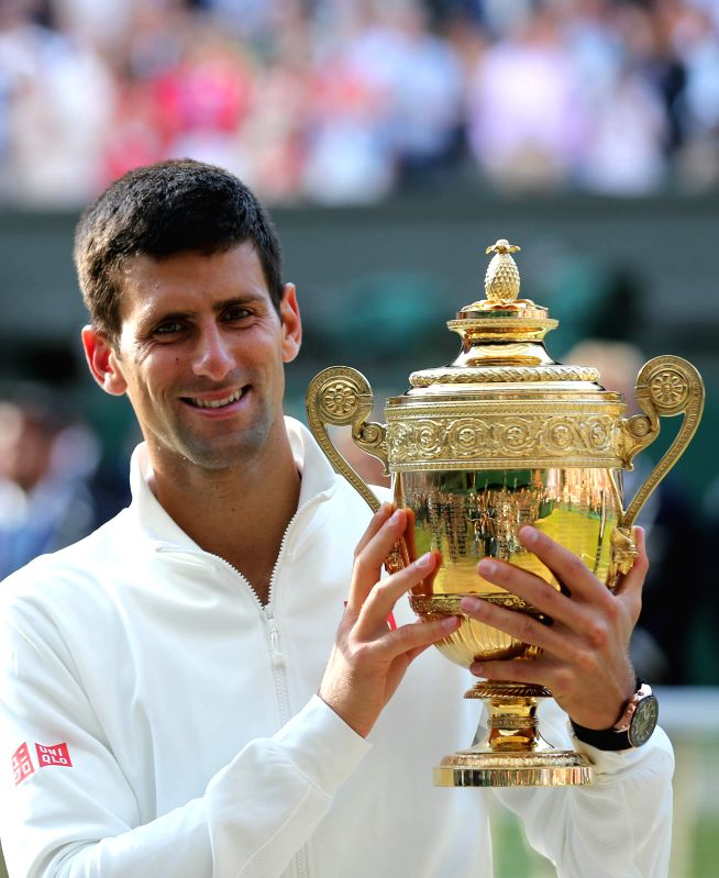 Serbia's Novak Djokovic holds the trophy after winning the men's singles final against Switzerland's Roger Federer at the 2014 Wimbledon Championships in Wimbledon, ..