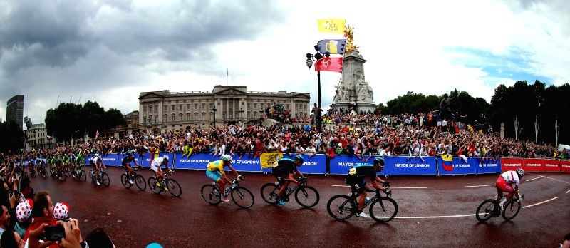 Chris Froome (3rd R) passes by the Buckingham Palace in Stage Three of the Tour de France, in London, on July 7, 2014.