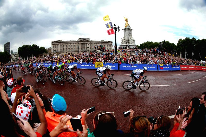 Contestants pass by the Buckingham Palace in Stage Three of the Tour de France, in London, on July 7, 2014.