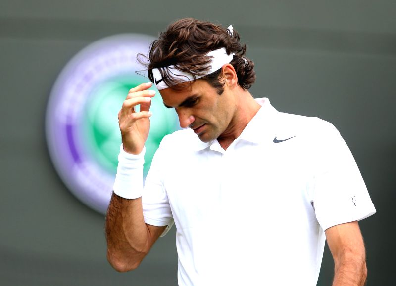 Switzerland's Roger Federer reacts during their men's singles first round match against Italy's Paolo Lorenzi at the 2014 Wimbledon Championships in London, Britain,