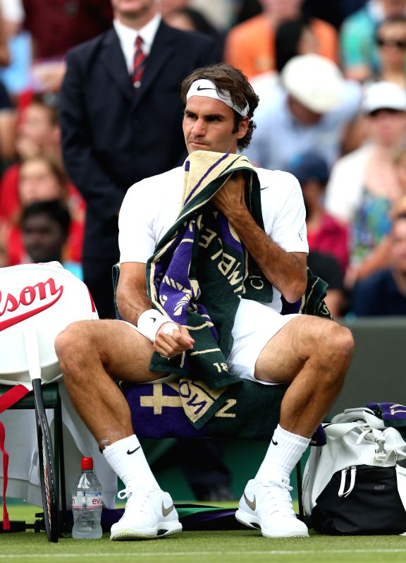 Switzerland's Roger Federer takes a rest during their men's singles first round match against Italy's Paolo Lorenzi at the 2014 Wimbledon Championships in London, ...