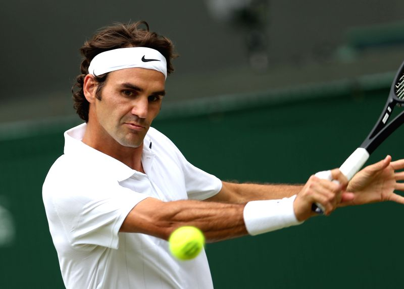 Switzerland's Roger Federer returns to Italy's Paolo Lorenzi during their men's singles first round match at the 2014 Wimbledon Championships in London, Britain, on .