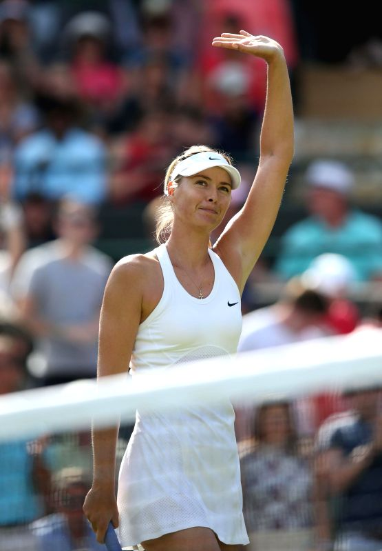 Maria Sharapova of Russia greets the audience after winning the women's singles first round match against Samantha Murray of Britain at the 2014 Wimbledon ...