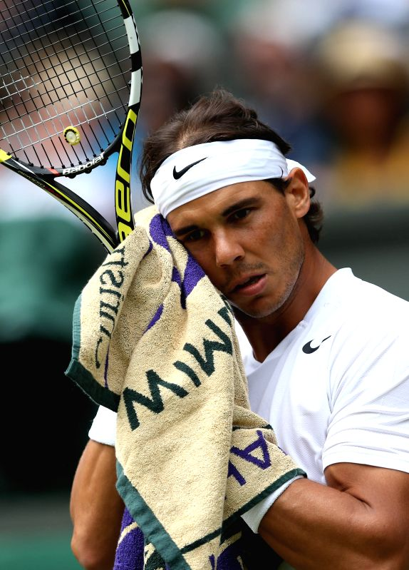 Spain's Rafael Nadal wipes with towel during the men's singles second round match against Czech Republic's Lukas Rosol at the 2014 Wimbledon Championships at ...