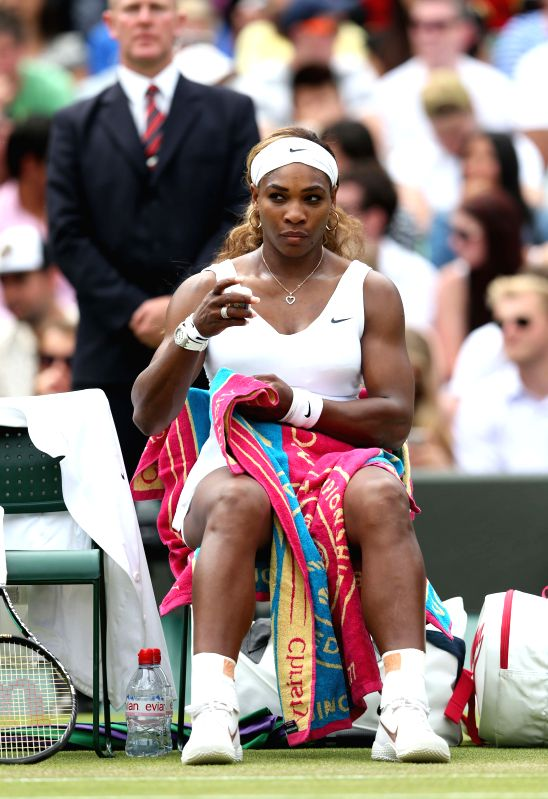 U.S. player Serena Williams rests during the women's singles second round match against South Africa's Chanelle Scheepers at the 2014 Wimbledon Championships in ...