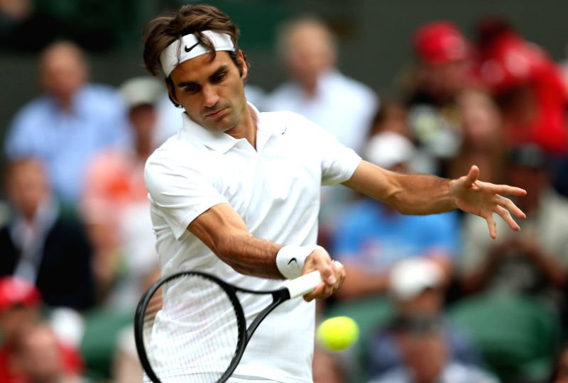 Switzerland's Roger Federer returns the ball during the men's singles second round match against Luxembourg's Gilles Muller at the 2014 Wimbledon Championships in ...