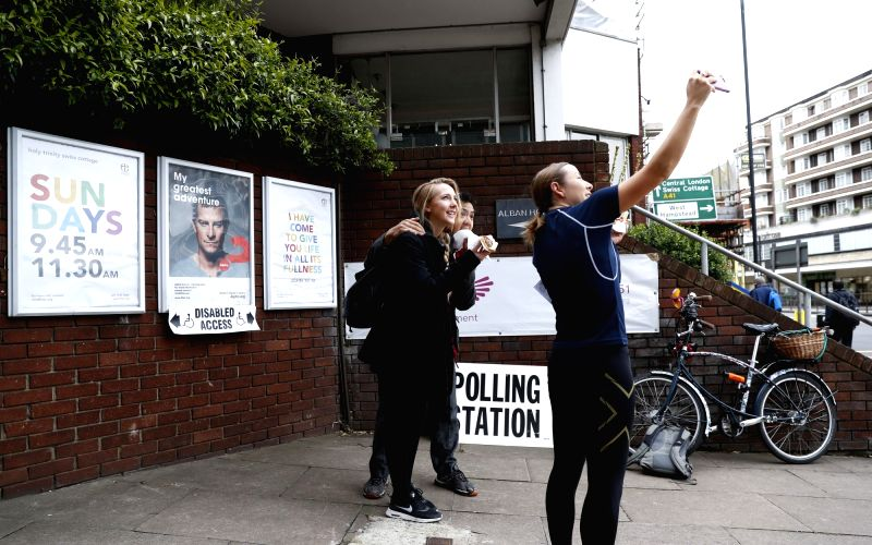 LONDON, June 8, 2017 - People pose for a selfie outside a polling station in London, Britain, June 8, 2017. Polling stations across Britain opened early Thursday as voters started to make their ...