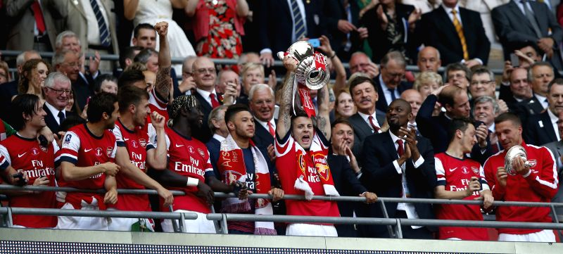 Jack Wilshere  of Arsenal lifts the trophy after FA Cup final between Arsenal and Hull City at Wembley Stadium in London, Britain, on May 17, 2014. Arsenal ended ...