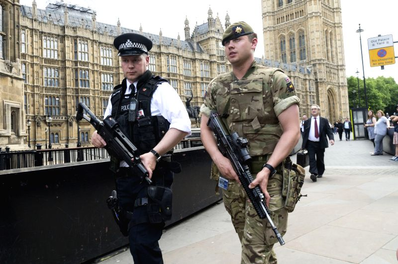 LONDON, May 24, 2017 - An armed soldier and an armed police officer patrol outside the Houses of Parliament in London, Britain, on May 24, 2017. British Prime Minister Theresa May announced Tuesday ... - Theresa May