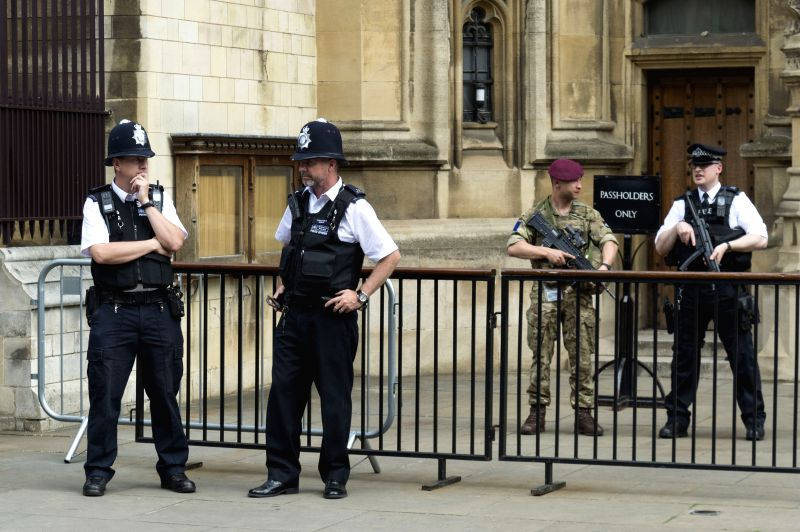 LONDON, May 24, 2017 - An armed soldier and armed police officers stand guard outside the Houses of Parliament in London, Britain, on May 24, 2017. British Prime Minister Theresa May announced ... - Theresa May