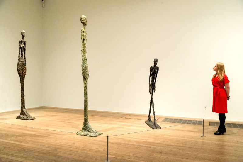 LONDON, May 8, 2017 - A gallery staff member views a selection of sculptures by artist Alberto Giacometti showing as part of a retrospective of his work at the Tate Modern in London, Britain on May ... - Alberto Giacometti