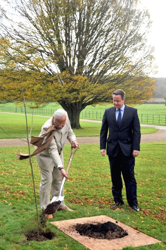 London (UK): Prime Minister Narendra Modi plants a sapling during a private tete-a-tete, at Chequers, in London on Nov 13, 2015. Also seen Prime Minister of United Kingdom (UK), David Cameroon. - Narendra Modi