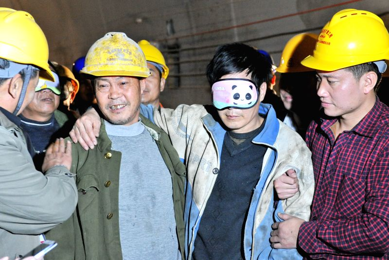 Longyan (China): Photo taken on Dec. 6, 2014 shows a trapped worker (2nd R) supported by his workmates after being rescued from the collapsed expressway tunnel under construction in Longyan, ...