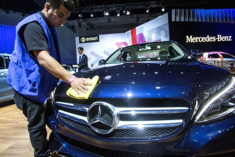 Los Angeles: A worker dusts off a new Mercedes-Benz C300 during the media preview day at the 2014 Los Angeles Auto Show in Los Angeles, on Nov. 19, 2014. )