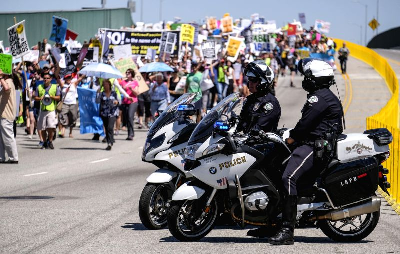LOS ANGELES, April 30, 2017 - Policemen guard at the site of a demonstration against President Donald Trump's climate policies in Los Angeles, the United States, April 29, 2017. Huge crowds took to ...