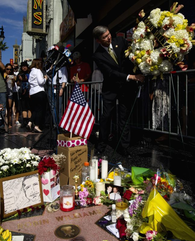 Leron Gubler (front), president and CEO of the Hollywood Chamber of Commerce, presents a flower wreath at Robin Williams' star on the Hollywood Walk of Fame in .